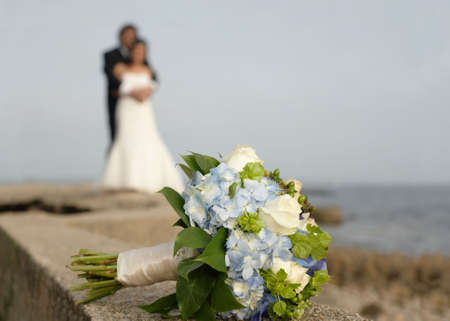Wedding bouquet with bride and groom in background Archivio Fotografico