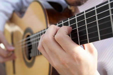 ballad: Closeup of mans hands playing classical acoustic guitar DOF focus on hand