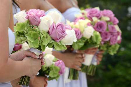 Row of bridesmaids holding bouquets at wedding ceremony Stock Photo