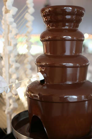 Chocolate fondue fountain with marshmallow being dipped Stock Photo