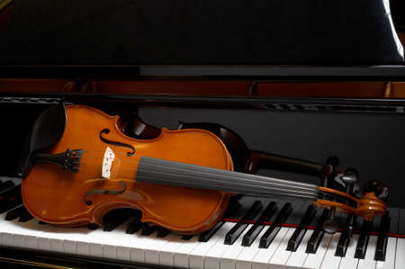 violins: Violin resting on keys of ebony grand piano Stock Photo