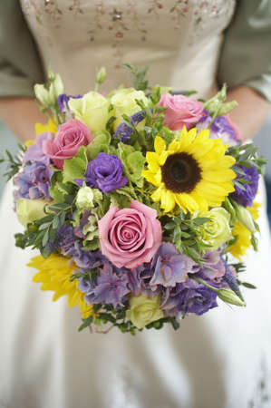 Bride holding colorful wedding bouquet of roses and daisies