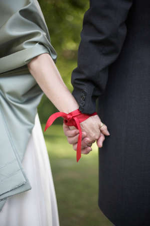 Hands tied with ribbon at wedding hand fasting ceremony