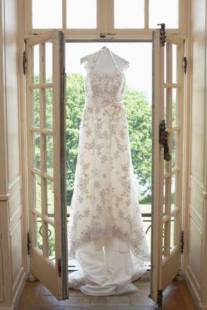 White wedding dress hanging in bridal suite