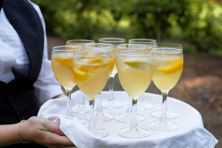 hands  hour: Glasses of mimosa being served at cocktail hour