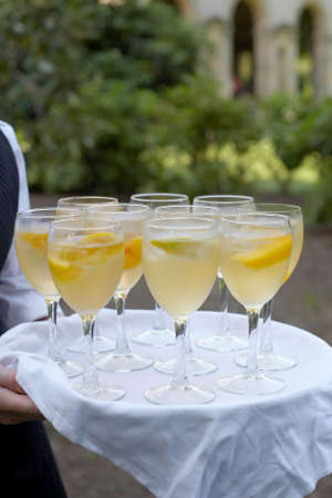 Glasses of mimosa being served at formal party photo