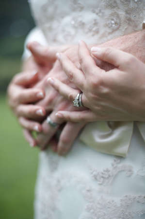 fidelity: Bride and groom hands over wedding dress focus on diamond ring