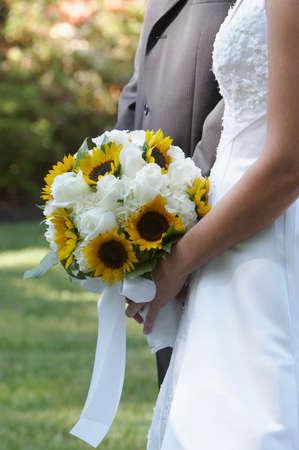 Bride holding wedding bouquet flowers against dress