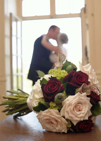 Wedding bouquet with bride and groom in background Stok Fotoğraf