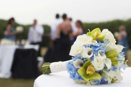 Bridal bouquet with wedding party in background focus on flowers