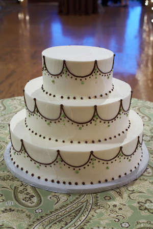Closeup of wedding cake with white and brown frosting