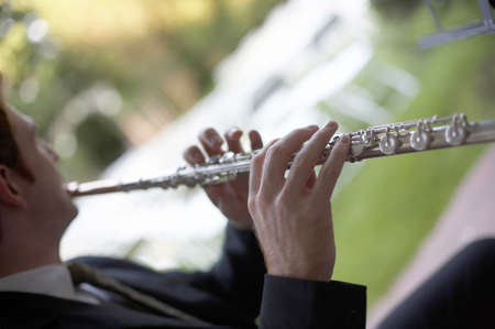 musicality: Man playing flute DOF focus on hand Stock Photo