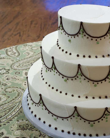 topper: Closeup of wedding cake with white and brown frosting