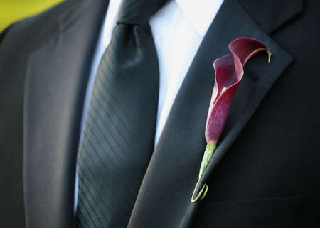 Purple calla lily wedding boutonniere on suit of groom