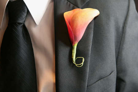 Calla lily wedding boutonniere on suit of groom