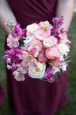 Bridesmaid holding colorful wedding bouquet against dress photo