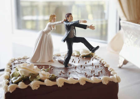 Funny wedding cake top bride chasing groom Stock Photo - 3729946