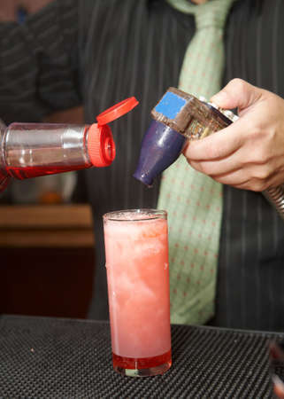 barkeep: Bartender pouring mixed drink at cocktail hour Stock Photo