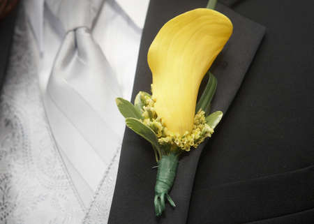 Yellow calla lily wedding boutonniere on suit of groom photo