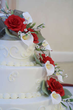 White wedding cake with red roses on table at reception photo