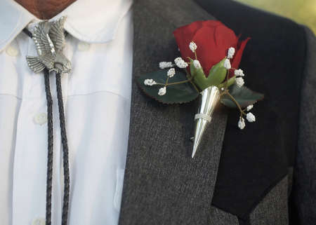 boutonniere: Bolo tie with classic red rose wedding boutonniere