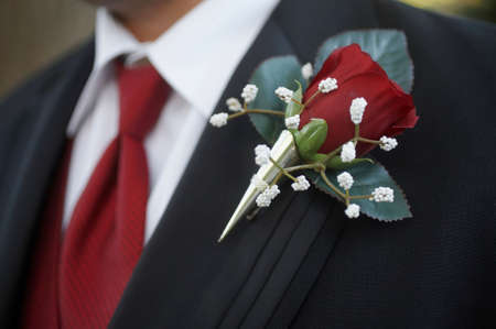 Classic red rose wedding boutonniere on suit of groom