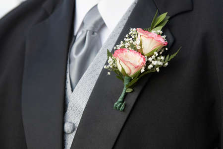boutonniere: Pink rose wedding boutonniere on suit of groom