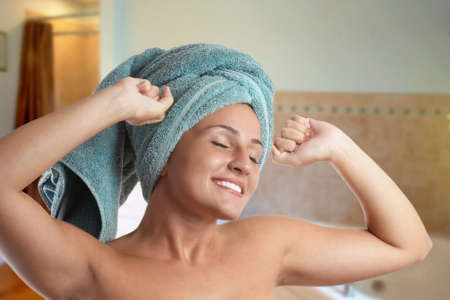 Beautiful young woman with towel stretching after shower photo