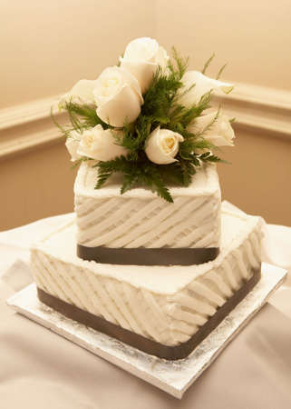 Wedding cake with white roses on reception table Imagens