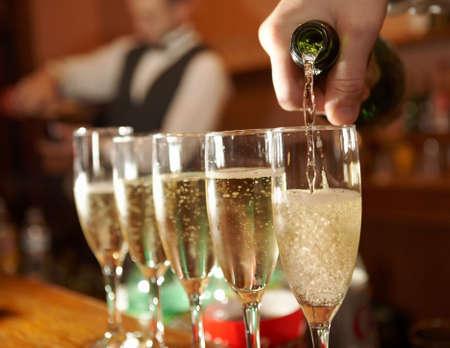 brindisi champagne: Mano del barista versando bicchieri di champagne