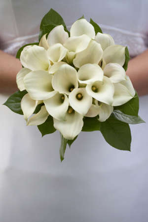 Bride holding wedding bouquet of white calla lilies