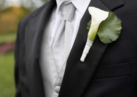 White calla lily boutonniere on suit jacket of groom photo