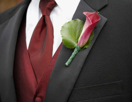 Red calla lily wedding boutonniere on suit jacket of groom