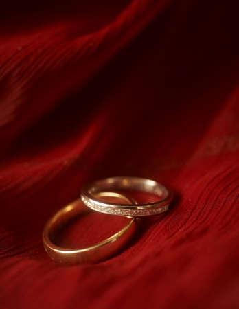 Close-up van huwelijks ringen op rood fluweel DOF focus op diamanten Stockfoto
