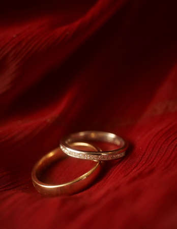 Closeup of wedding rings on red velvet DOF focus on diamonds
