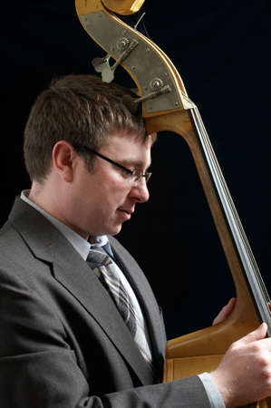 Portrait of musician leaning against upright bass photo
