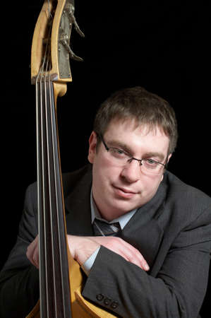 virtuoso: Upright bass virtuoso leaning against his instrument Stock Photo