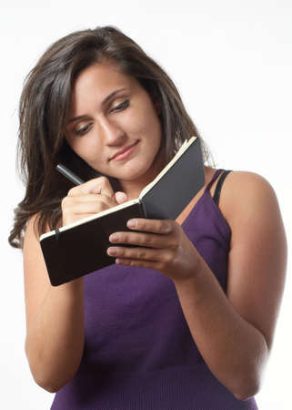 Pretty young woman writing notes in little black book Stock Photo - 4024819