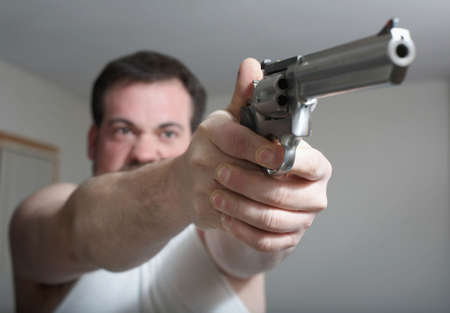 violence and trigger: Man shooting a gun focus on hands
