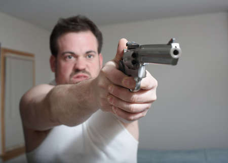 Man in home aiming gun ready to fire focus on hands