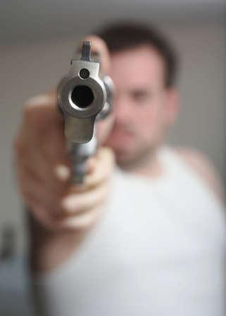 Anonymous man aiming gun at the viewer