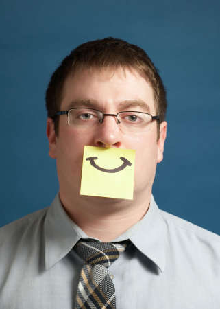 Businessman with smiley yellow sticky note on face photo