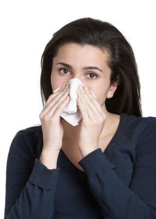 Pretty young woman with a cold blowing nose photo