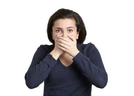 Attractive young woman with hands over mouth speak no evil photo