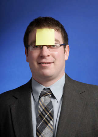 Silly businessman with yellow sticky note on forehead photo