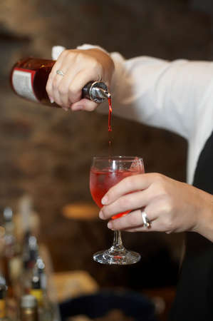 barkeep: Bartender pouring bottle into red cosmopolitan mixed drink