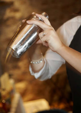 Hands of bartender in motion shaking up martini shaker