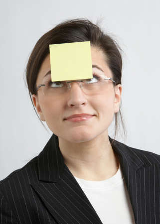 Funny businesswoman with yellow sticky note on forehead photo
