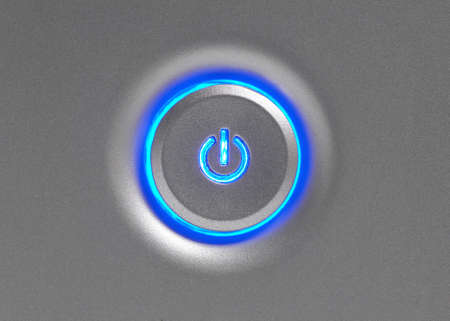 blue button: Blue glowing power button closeup on computer