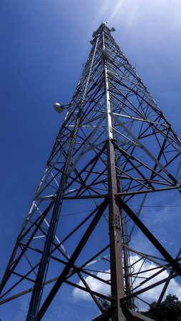 Tall metal tower with bouncing signal antennas, seen from the surface, with blue sky in the background and few clouds